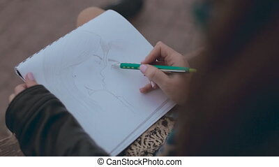 Close up of girl which drawing a picture of kissing couple on a bench