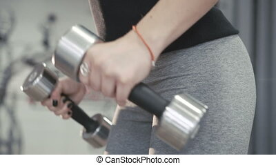 Close up of girl working out with dumb-bell for delta muscles in 4K