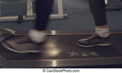 Close-up of girl's feet on the treadmill