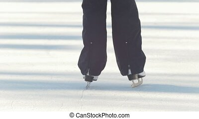 Close-up of girl's figure skates skating on the ice rink