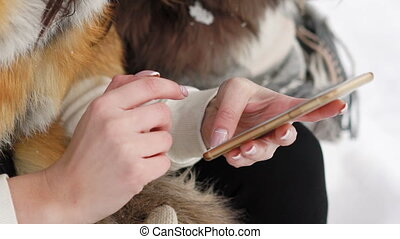 Close up of girl's hands using mobile phone outdoor in winter
