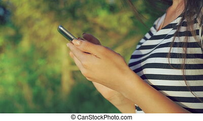 Close up of girl's hands using phone in the green summer park. 4k