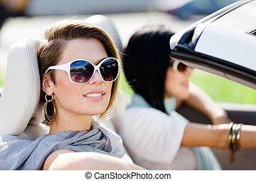 Close up of girls in sunglasses in the convertible car -...