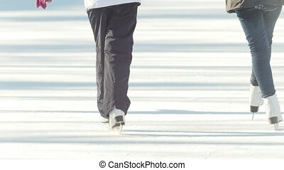Close-up of girl's legs in figure skates skating on the ice...