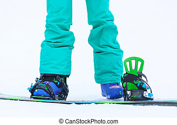Close up of girl`s legs with snowboard and bindings.