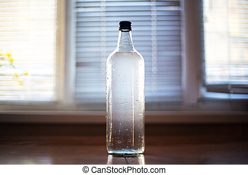 Close-up of glass bottle with water on blurred background.