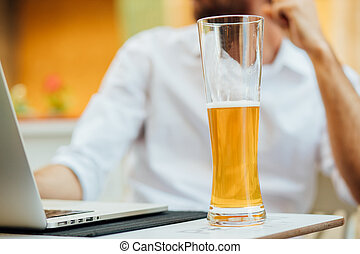 close up of glass of beer on table outside