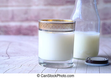 Close up of glass of milk and jar on table
