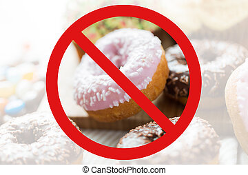 close up of glazed donuts pile behind no symbol