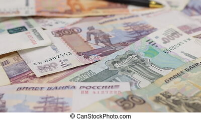 Close-up of gold pen lying on rubles.
