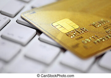 Close up of golden credit card on a computer keyboard. Concept of internet purchase