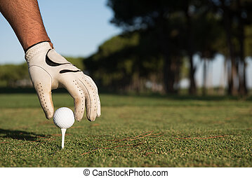 close up of golf players hand placing ball on tee - closeup...