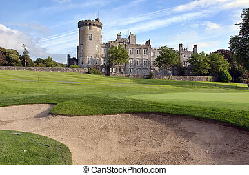 close up of golf sand bunker by golf green and castle