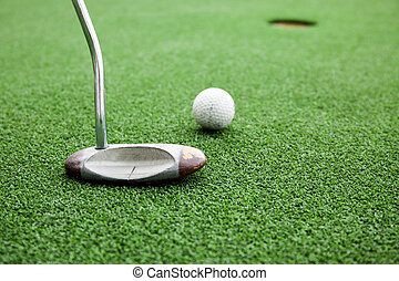 Close-up of golfer playing a golf in green grass field