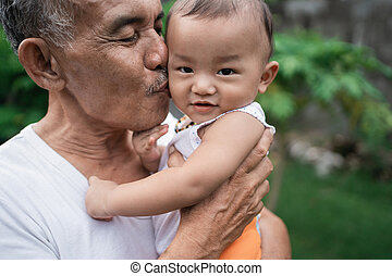 close up of grandfather carried and kissed the little grandson