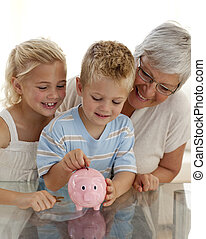 Close-up of grandmother and children saving money