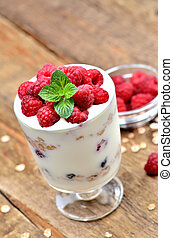 Close-up of greek yoghurt with oatmeal and fresh raspberries in a glass and mint leaves - vertical photo