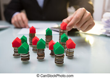 Close-up Of Green And Red House Model On Stacked Coins