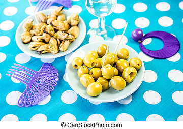 Close-up of green olives, mussels and costume jewelry