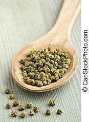 green pepper in a wooden spoon