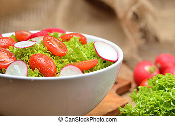 Close-up of green salad Lollo Biondo with tomatoes and radishes in a white bowl on wooden table, a pitcher of oil in the background - vertical photo