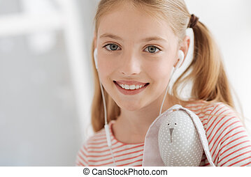 Close up of grey eyed girl with toy enjoying music