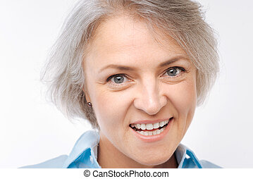 Close up of grey-haired woman grinning at camera