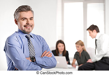 Close up of Grown up smiling successful business man. Standing on foreground and business team discussion on background