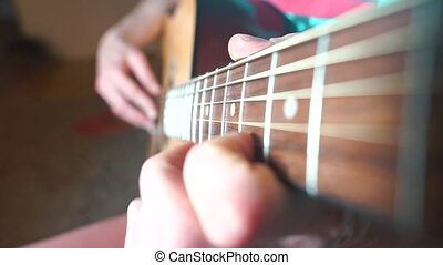 Close-up of guitarist fingers on guitar.