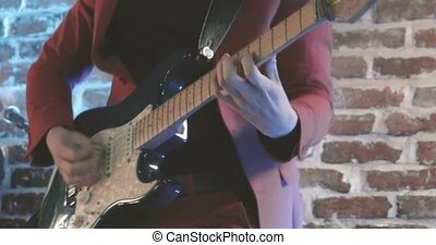 Close up of guitarist on stage play on guitar with mediator, vintage color