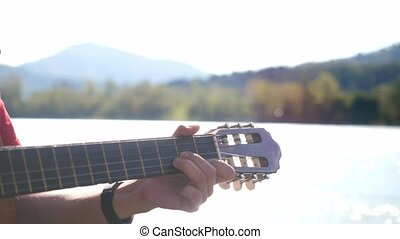 Close up of guy's hand plays on a guitar sitting by mountain...