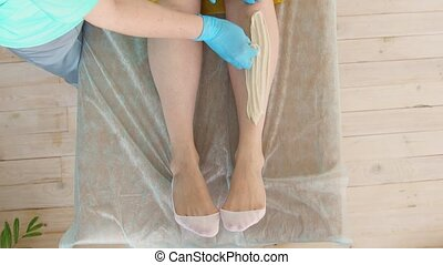 Close-up of hair removal master removes leg hair using...