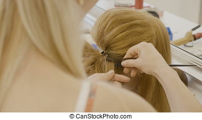 Hairdresser making a hairstyle in the salon