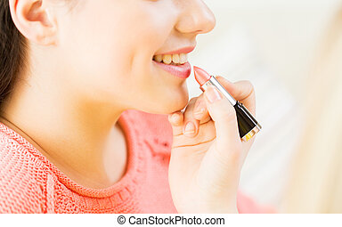 close up of hand applying lipstick to woman lips