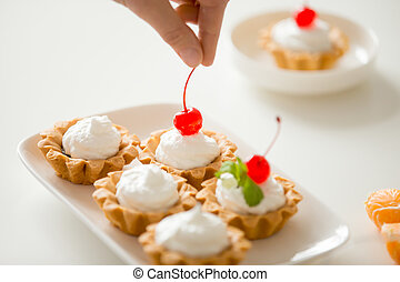 Close up of hand decorating mini cream tarts with cherry
