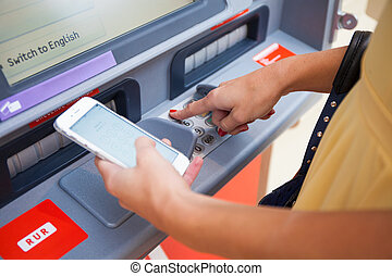 Close up of hand entering pin at an ATM. Finger about to press a pin code on a pad