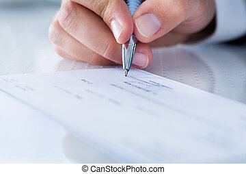 Close-up Of Hand Filling Cheque - A Male Hand Filling Out ...