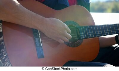 Close up of hand guy plays on a guitar sitting by mountain...
