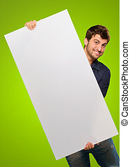 Close-up Of Hand Holding Blank Placard On Green Background