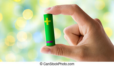 close up of hand holding green alkaline battery - recycling,...