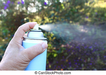 spraying pesticide - close-up of hand holding spray can, ...