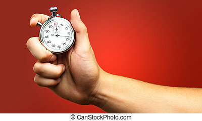 Close Up Of Hand Holding Stopwatch against a red background