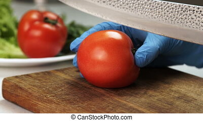 Close-up of hand in gloves with knife is cut ripe tomato.