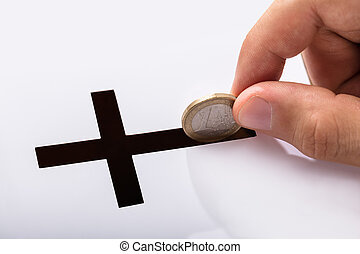 Hand Inserting Coin In Crucifix Slot - Close-up Of Hand...