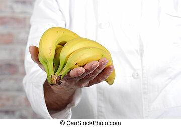 close up of hand man holding banana - close up of a hand man...
