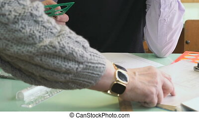 Close-up of hand of teacher and student on table - Geometry...