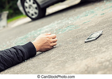 Close-up of hand of traffic victim and smartphone on the street