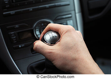 hand on manual gear shift knob - close up of hand on manual...