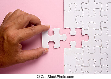 Close up of hand placing the last jigsaw puzzle piece on pink background. Business and team work concept.