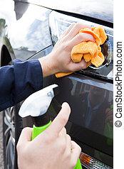 Close Up Of Hand Polishing Car Headlight Using Cloth